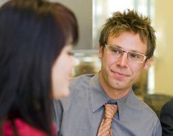 Man wearing glasses looking at out of focus woman