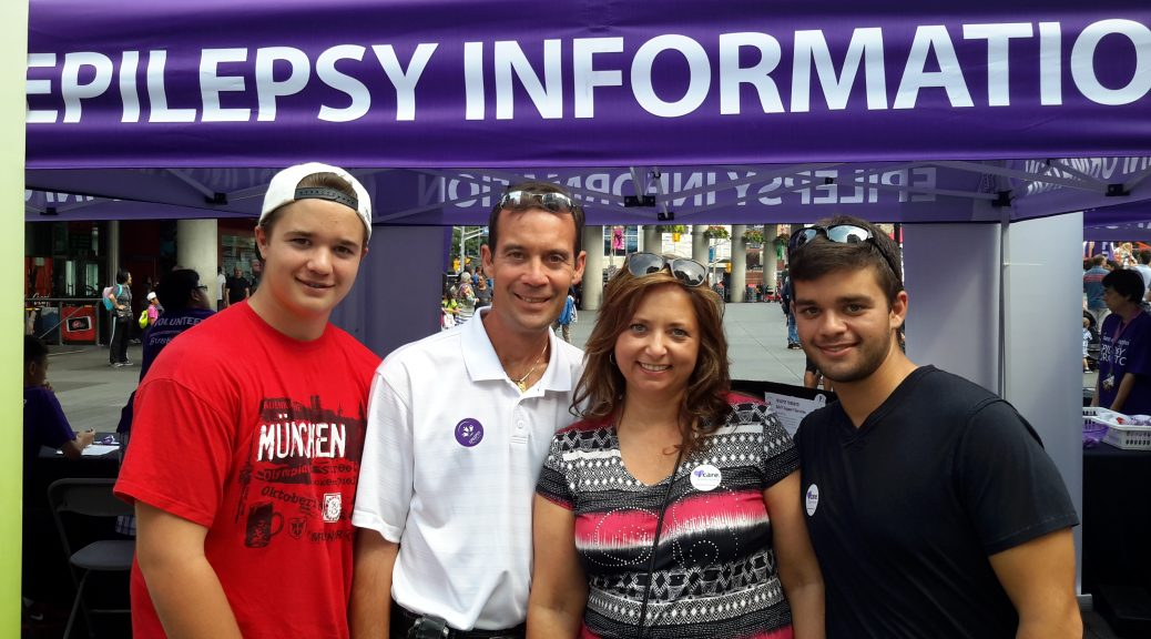 Four people smiling in front of Epilepsy information booth