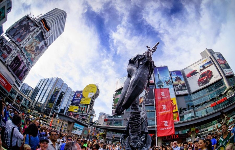 'Saurus' stiltwalker dinosaur performing in Yonge-Dundas Square at BuskerFest