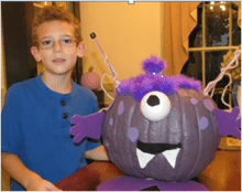 Boy with cyclon decorated purple pumpkin