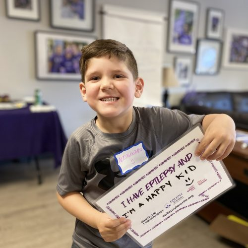 """Child holding a sign, """"I Have Epilepsy And...I'm a happy kid"""""""