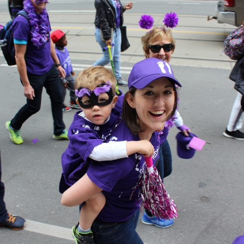 Woman with child on her back walking in the Purple Walk