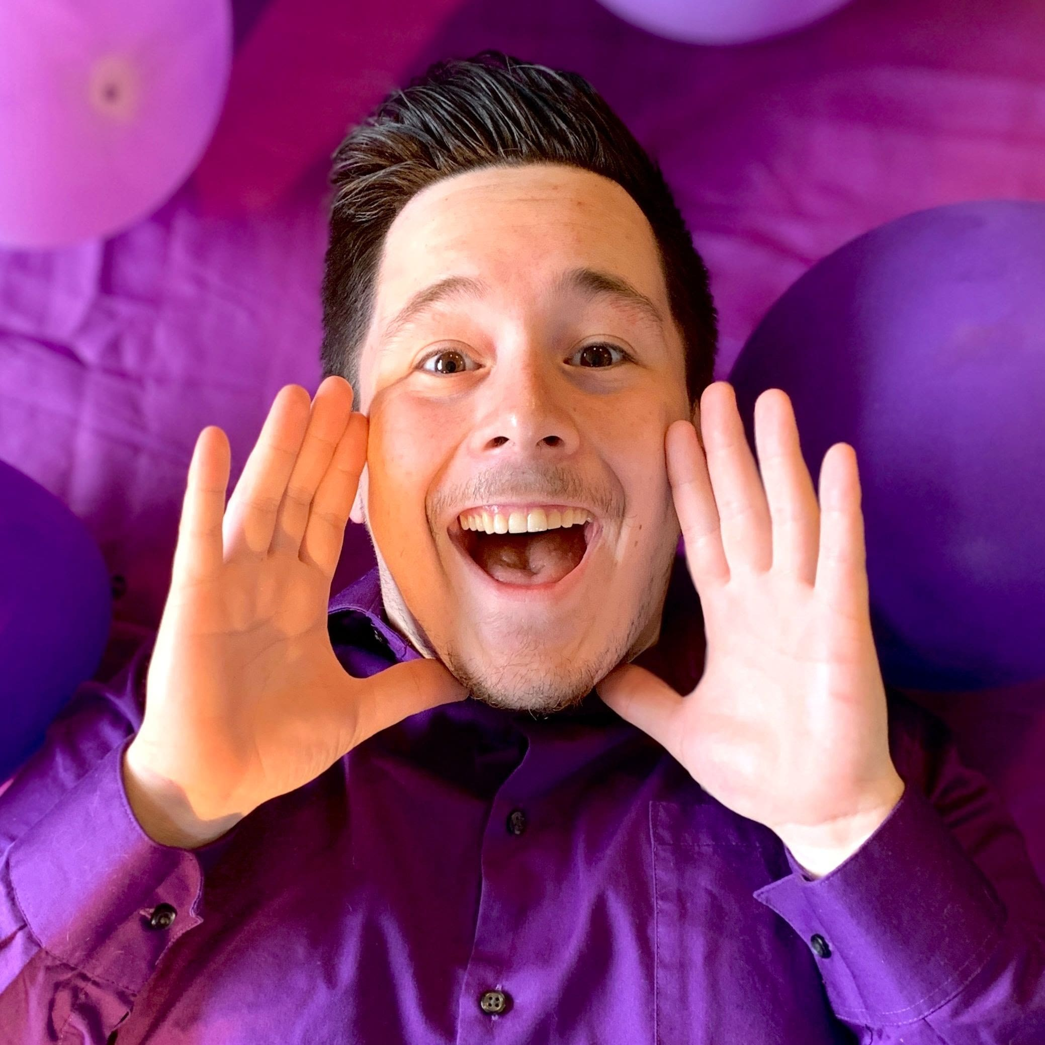 Smiling man in purple, surrounded by purple balloons, frames his face with his hands
